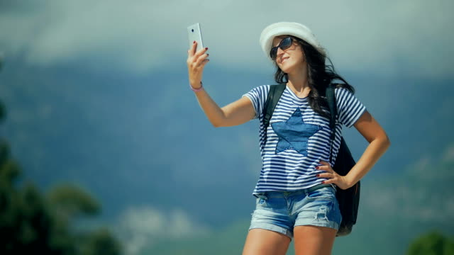 Pretty happy woman taking selfie photo with smart phone in the mountains. video