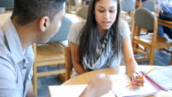 Pretty Hispanic teen girl in high school library studying with African American male student video