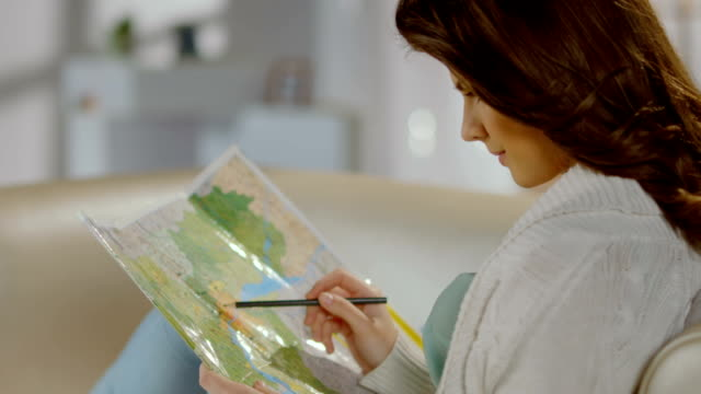 Pretty lady planning trip for weekend, vacation, studying map video
