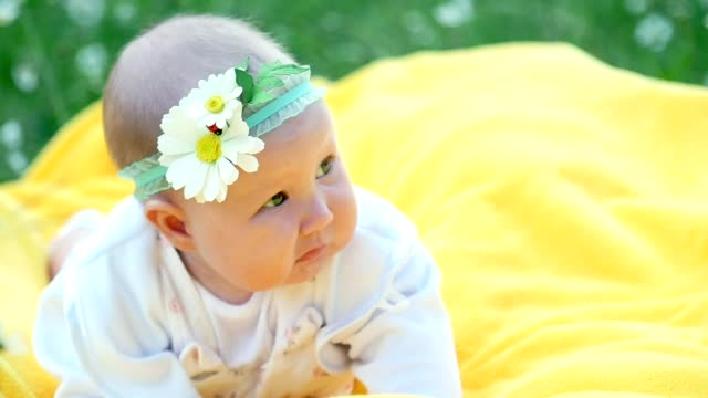 A pretty little girl, baby, lies on a yellow plaid, on the grass. On her head is a bandage with chamomile video