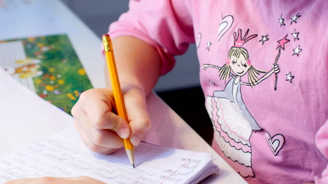 Pretty little girl is doing her homework at the table video