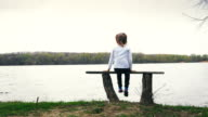 Pretty little girl sits on the bench near the river video