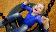 Pretty little girl stuck in the middle of a tire swing video