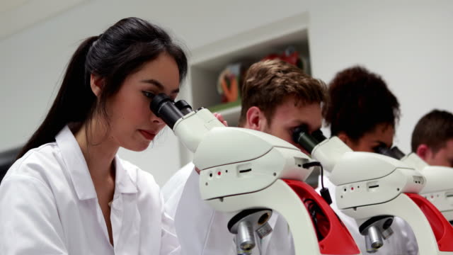 Pretty medical student looking through microscope then smiling video