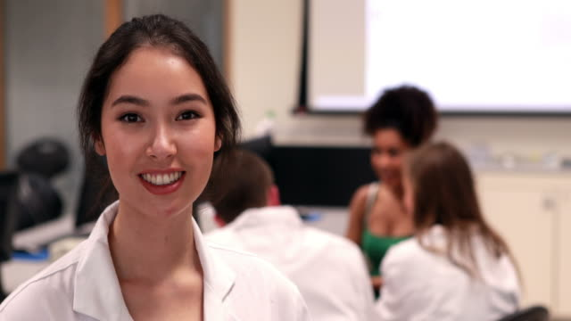 Pretty medical student smiling at camera in class video