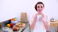 Pretty model standing in kitchen drinking mug of coffee video