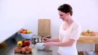 Pretty model standing in kitchen preparing an omelette video