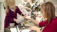 Pretty mother and small daughter in red dresses and Santa hats preparing and drinking tea near Christmas tree. video