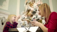 Pretty mother and small daughter in red dresses sitting at the table near Christmas tree. video