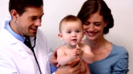 Pretty mother holding baby while pediatrician listens to chest video