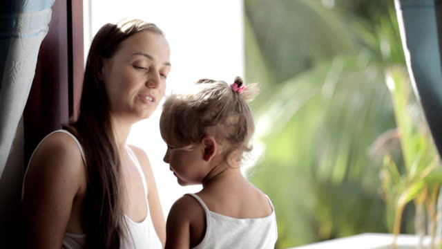 Pretty mother soothing and hugging crying baby girl. video