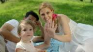 CLOSE UP, DOF: Pretty mum, happy dad and cheerful baby saying hi and waving video