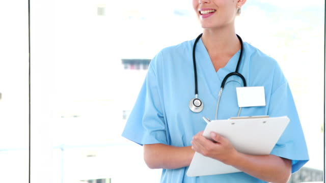 Pretty nurse looking at camera and writing on clipboard video