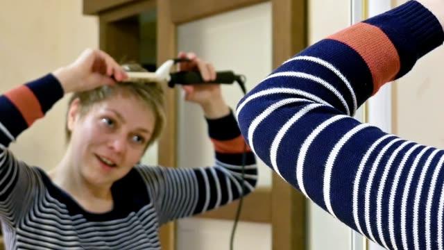 Pretty smiley blond short hair woman curls hair video