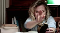 Pretty student fallen asleep on books at her desk and woken up by an alarm video