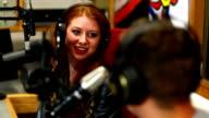 Pretty student interviewing someone for radio in the studio video