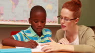 Pretty teacher helping pupil in classroom smiling at camera video