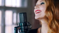 Pretty vocalist with bright make up perform on stage at concert microphone. Jazz video