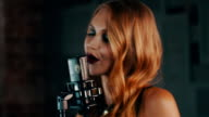 Pretty vocalist with dark lips perform on stage at concert microphone. Jazz video