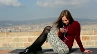 Pretty woman communicate by phone relax on bench video