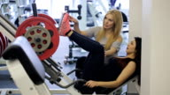 Pretty woman does exercises on simulator platform to train all muscles of legs video