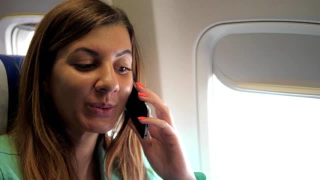 Pretty Woman Having Fun Talking On The Phone, Sitting In The Airplane Window video
