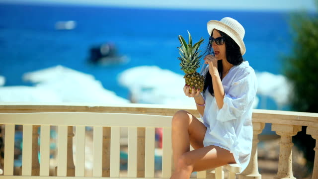 Pretty woman in white hat with tropical cocktail on the beach enjoying sunny weather looking at the ocean view. video