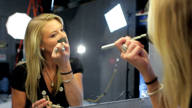 Pretty woman putting on makeup before a photo shoot video