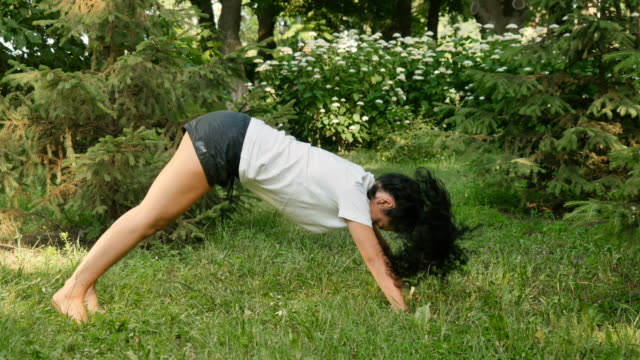 Pretty woman stretches her back and makes sport exercises in park video