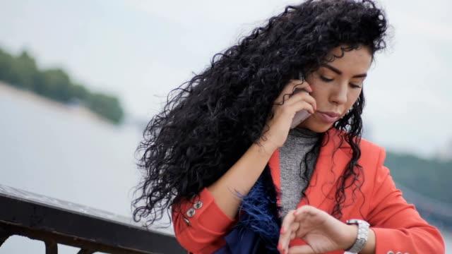 Pretty woman talks on the phone at the bridge video