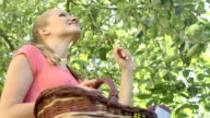 Pretty woman up on a ladder picking apples from an apple tree on a summer day video
