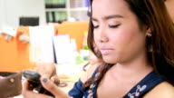 Pretty woman use smart phone in Salon video