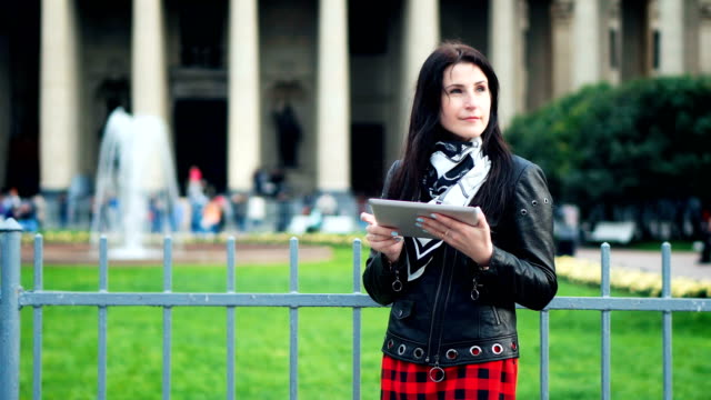 Pretty woman with a tablet in her hands looking for a road in a tourist city video