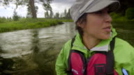Pretty young Asian woman rafts down a river in portrait video