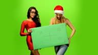 A pretty young brunette and blond womans in Santa hats, blank sign, green screen video