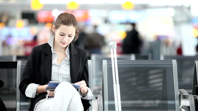 Pretty, young  businesswoman waiting for her flight on an airport video