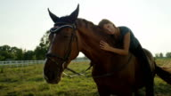 CLOSE UP: Pretty young Caucasian brunette girl laying on horse and cuddling him video