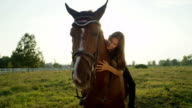 CLOSE UP: Pretty young Caucasian brunette girl sitting on horse and cuddling him video