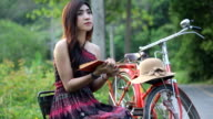 Pretty young female sitting near vintage bicycle and reading book video