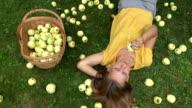 Pretty young gardener girl lying on grass near basket full of fruits and bit taste apple fruit video