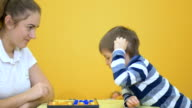 Pretty young girl playing checkers with little boy on yellow background video