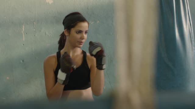 Pretty young hispanic woman training at boxing in gym video