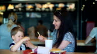 pretty young mother and child eating fast food video