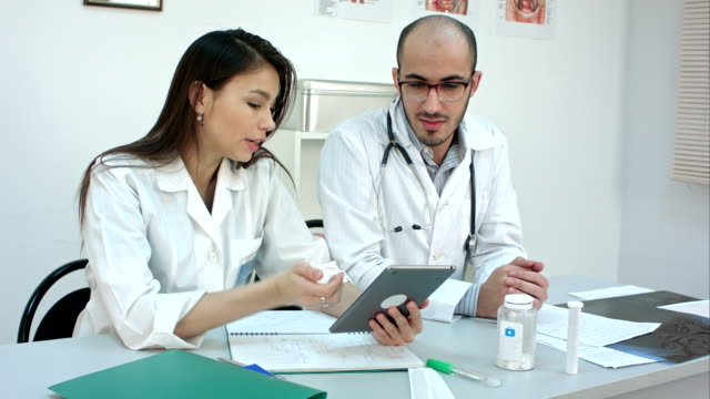 Pretty young nurse showing something on the tablet to her male colleague video