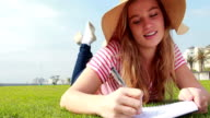 Pretty young student lying on the grass studying video
