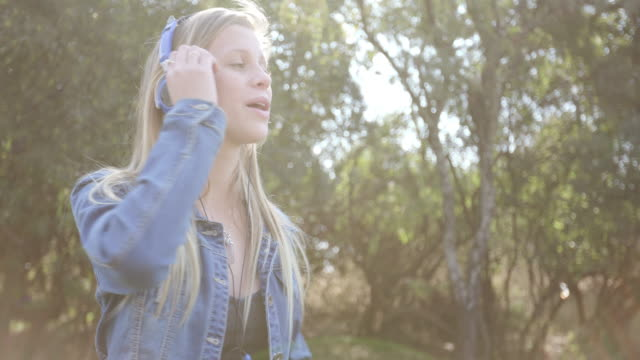 Pretty young teenage girl dancing with headphones on video