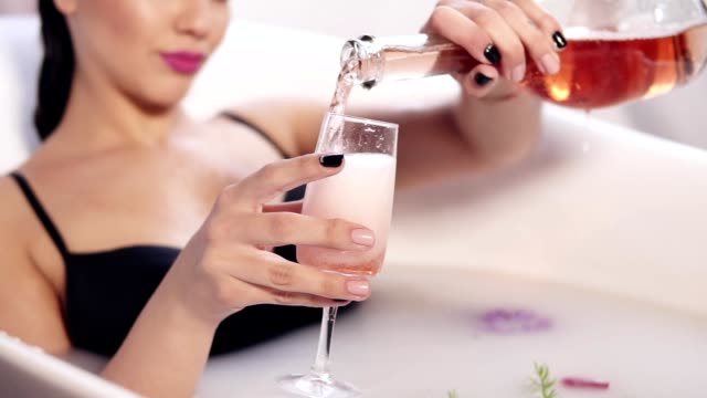 Pretty young woman bathing and relaxing with glass of champagne in the hot tub filled with milk and flowers. Beautiful woman pooring sparkling wine to the glass. Slowmotion shot video