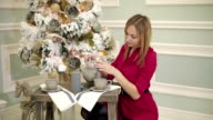 Pretty young woman in red dress sits at the table near New year tree and pours tea into a cup. video