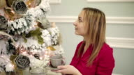 Pretty young woman in red dress sits at the table near New year tree and drinks tea or coffee. video