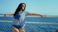 Pretty young woman posing during traveling by boat among the islands. video